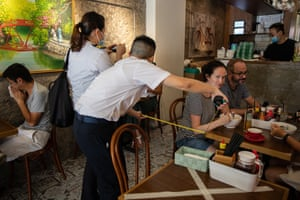 Officers with the Food and Environmental Hygiene Department measure the distance between tables in a restaurant in Hong Kong. According to guidelines, tables must be at least 1.5 metres apart.