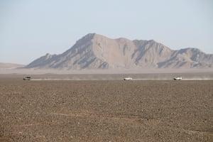 Support vehicles race across the flat desert plain heading towards Eye of the Lut.