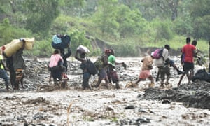 People cross the La Digue river in Haiti during heavy rain
