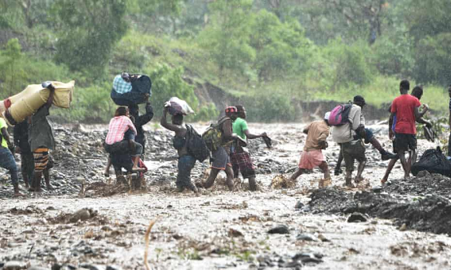 People cross the La Digue river in Haiti during heavy rain