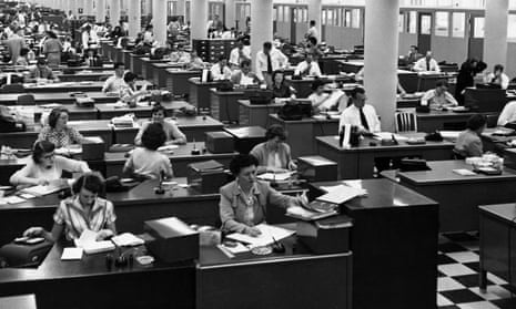 Lots of desks and office workers in an office in the 1950s