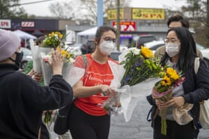 Roula AbiSamra, center, and Chelsey (last name withheld), right, prepare to lay flowers bouquets at a makeshift memorial outside of the Gold Spa.