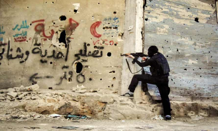 A fighter is seen in the Qaban neighborhood of Damascus shooting from around a corner.