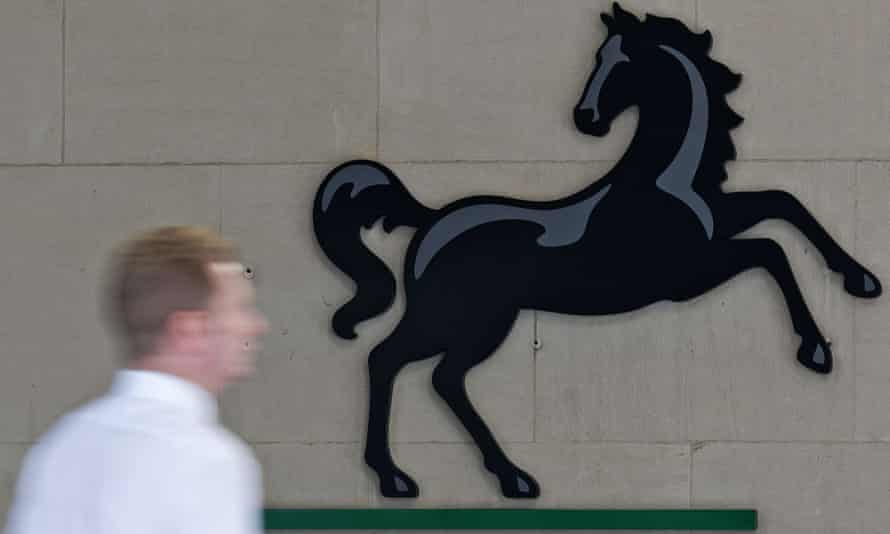 A man passes the Lloyds bank black horse sign