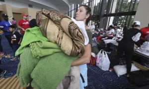 Volunteer Judy Segar carries donated blankets for victims of the flooding, at Lakewood.