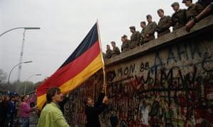 The German national flag is waved at East German border guards at the Berlin Wall, November 1989