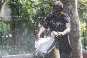 A man uses a park sprinkler to cool off.