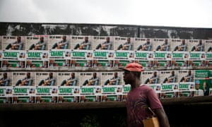 A man in Lagos walks past posters for the Nigerian president, Muhammadu Buhari, during his election campaign of 2015