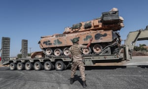 A soldier directs a Turkish military vehicle carrying tanks near the Syrian border.