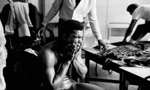 Cassius Clay splashes his face as he gets dressed after training.