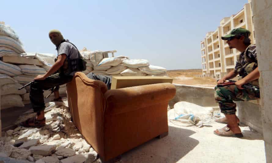 Jabhat al-Nusra fighters rest behind sandbags in Aleppo