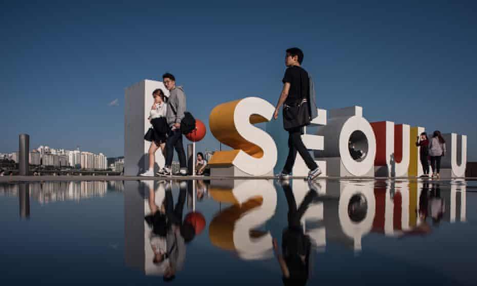 People pose for photos before a sculture reading 'I Seoul U' at Yeouido park