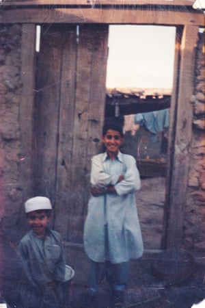 Gulwali Passarlay, 10, as an apprentice tailor with his younger brother Nasir.