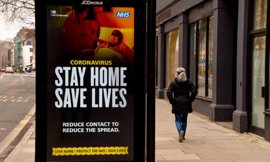 A woman walks past a 'Stay Home Save Lives' sign in Central London