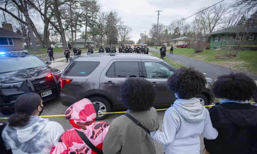 People stand behind a line of police tape at the scene where Daunte Wright was shot and killed by police. On Monday afternoon, police released graphic body-camera footage of the incident.