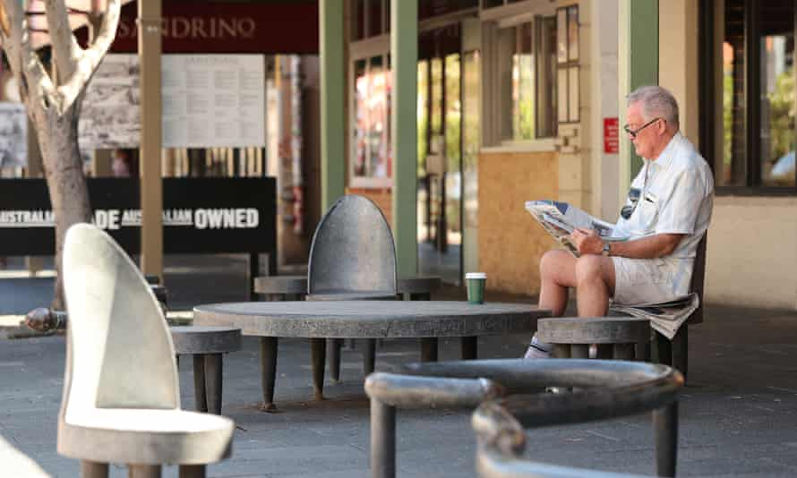 A man reads a local newspaper in a deserted Fremantle street
