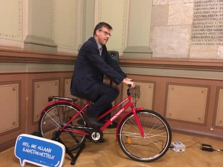 Мэр Кари Карьялайнен использует статический велосипед для включения системы громкой связи на Зимнем велосипедном конгрессе.