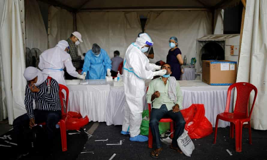 Healthcare workers at a Delhi bus terminal test for coronavirus amid a surge of cases in India.