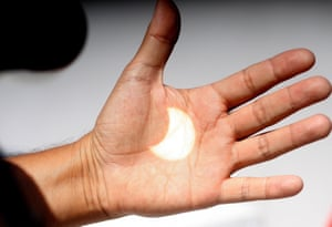 An image of the solar eclipse is projected onto a hand in Ensenada, Baja California, Mexico.