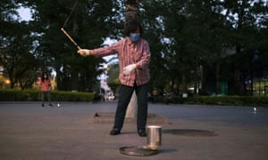 A woman wearing a face mask whips a spinning top at a square in Beijing, China 28 April 2020.