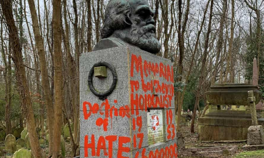 Karl Marx's tomb with slogans in red daubed on stone under large bust of philosopher's head.