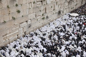 Orthodox Jews cover their heads with prayer shawls as they recite the Priestly Blessing on the high holiday of Passover, in front of the Western Wall in Jerusalem, Israel
