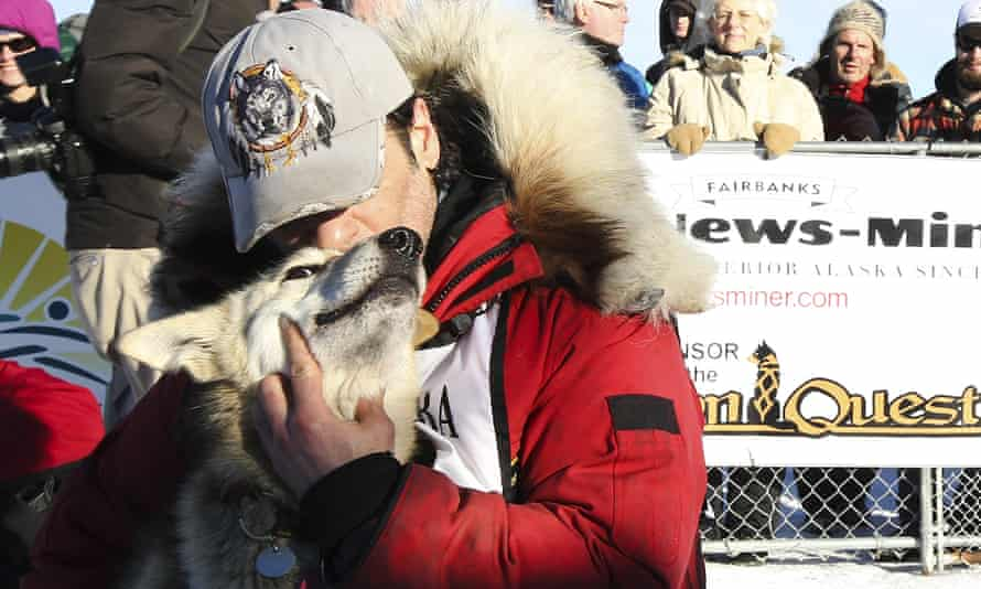 Hugh Neff hugs his lead dog, George, after, winning the Yukon Quest sled dog race.