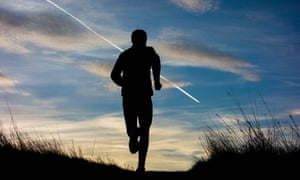 Man jogging uphill on country trail silhouetted against dawn sky at sunrise