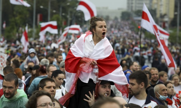 Protestor, draped in Belarusian flag, shouts from the shoulders of those in a large crowd.