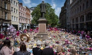 People gather to see flowers and messages of support in St Ann's Square in Manchester.