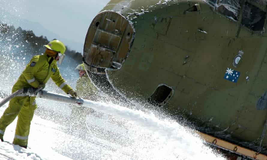 A firefighter quenches the underside of a plane with foam.