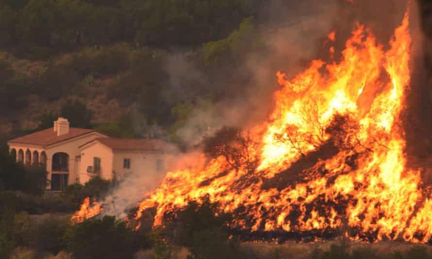 Flames from a back firing operation rise behind a home in Santa Barbara, California.