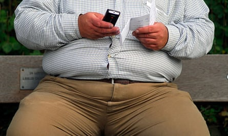 Obese man sending a text message from mobile phone