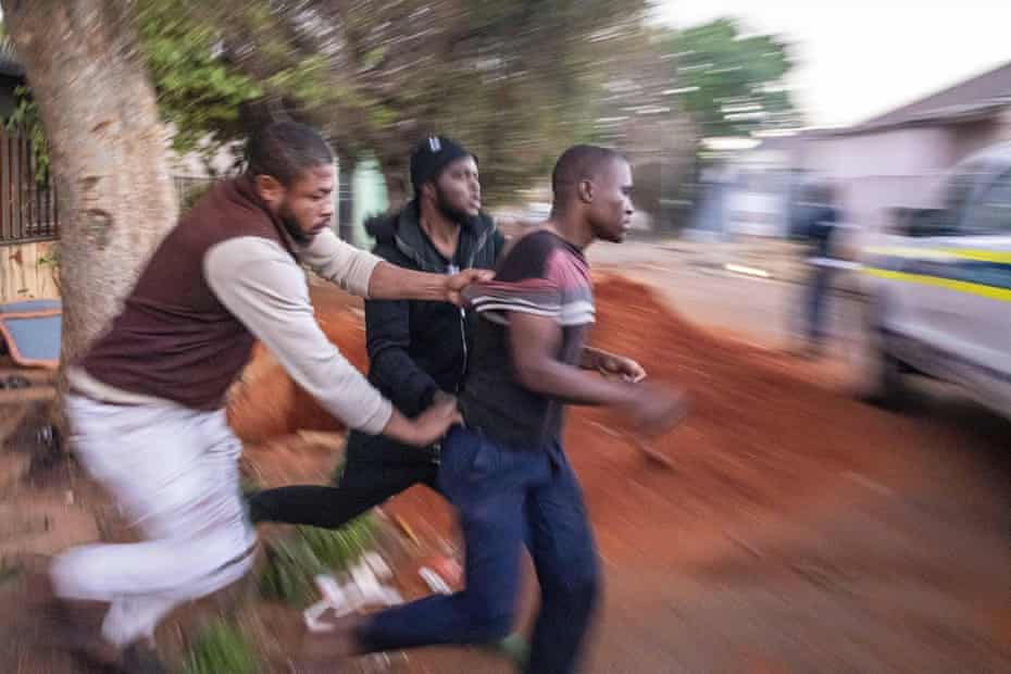 Nigerian foreign nationals remove a looter from their shops in Troyeville, Johannesburg