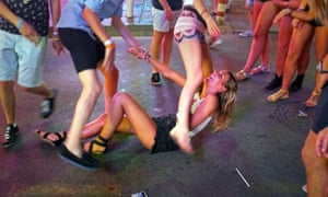 A girl laughs as she sits on the pavement in Punta Ballena in Magaluf