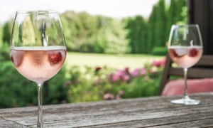 rose wine glasses on a wooden table at garden in summer