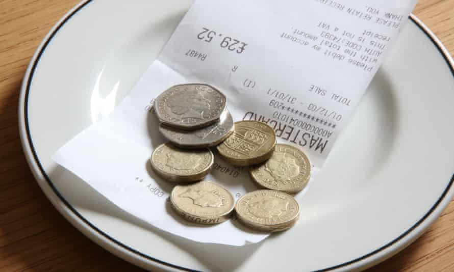 pound coins on a plate as a tip to a waiter