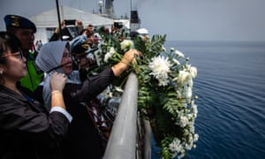 A family of victims of Lion Air flight JT 610 throw a flowers at the crash site a month after the accident.