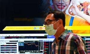 A man wearing a protective face mask in the Bangkok stock exchange in Thailand