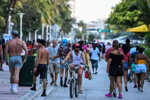 A man rides a bicycle as people walk on Ocean Drive in Miami Beach, Florida on June 26, 2020. Florida has registered more than 15,000 new cases of coronavirus in a day, easily breaking a record for a US state previously held by California, according to official numbers published on July 12, 2020.