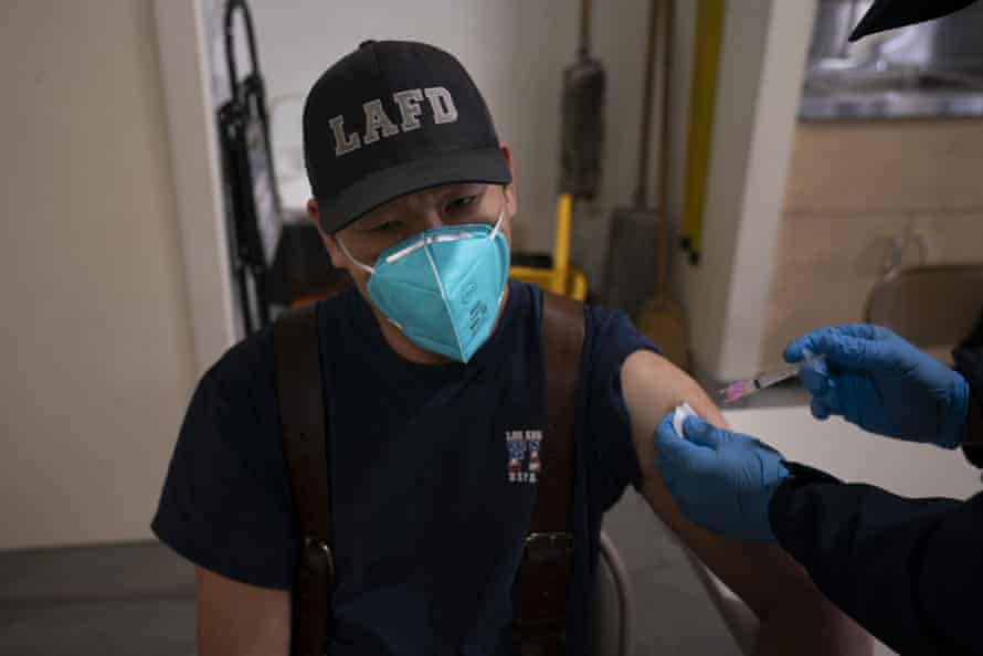 Henry Xie, a Los Angeles firefighter, receives a second dose of Covid-19 vaccine at a Los Angeles fire station.
