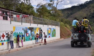 People paint a mural alluding to peace on the road leading to Planadas, Tolima department, Colombia.