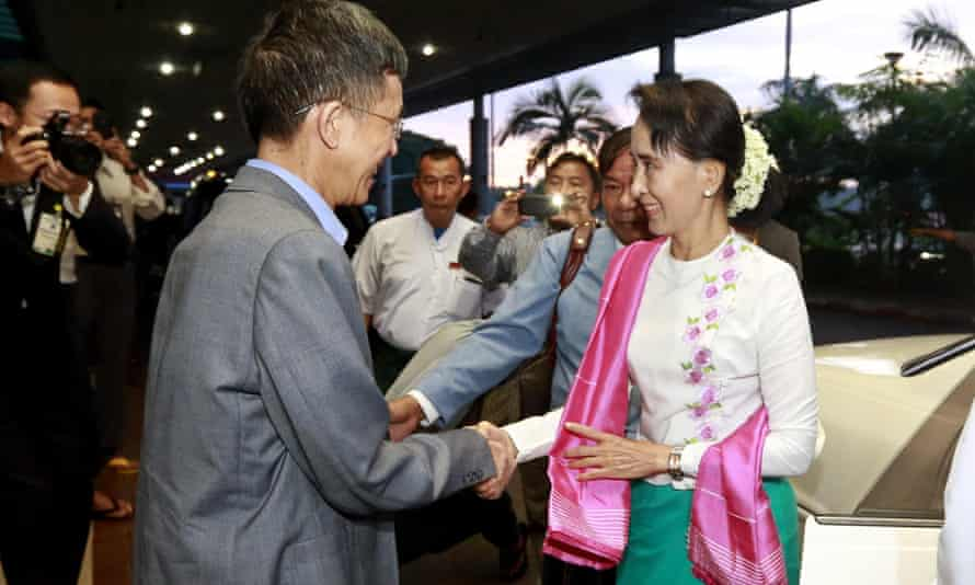 The Burmese opposition leader, Aung San Suu Kyi, is greeted by the Chinese ambassador to Burma, Yang Houlan, before her departure for China, at Yangon International Airport on Wednesday.