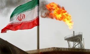 A gas flare on an oil production platform in the Soroush oilfields alongside an Iranian flag in the Gulf.