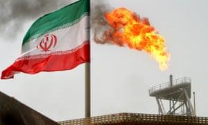 A gas flare on an oil production platform alongside an Iranian flag
