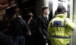 A police officer reminds workers in Newcastle city centre on Saturday 10 October of the 10pm curfew.