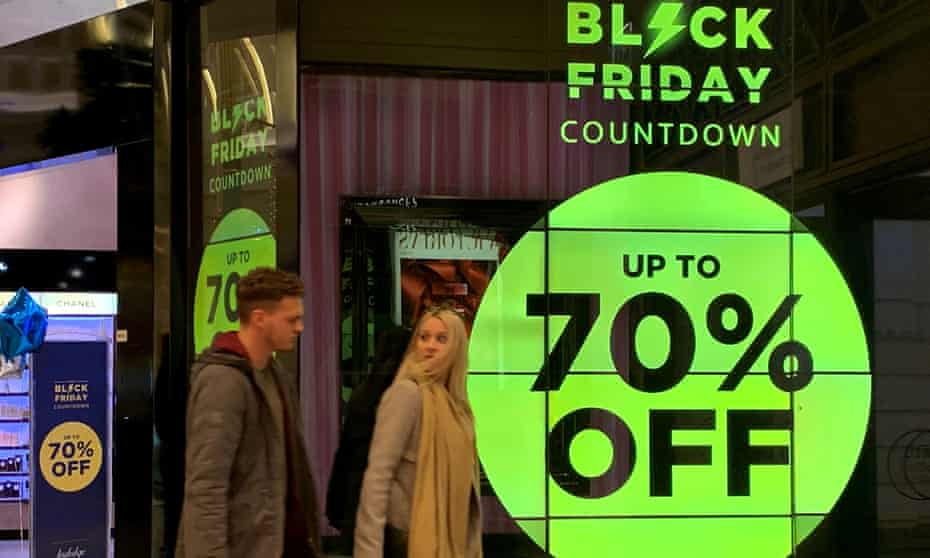 People walk past a sign advertising Black Friday offers at a perfume shop in Manchester