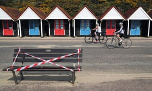 Cyclists making their way past a taped off bench on the sea front on Bournemouth beach on July 4, 2020