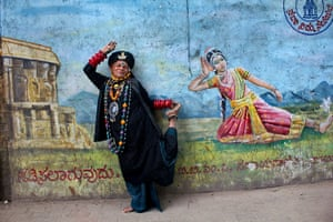 A migrant poses in front of a mural in Bengaluru