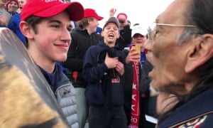A student from Covington Catholic high school stands in front of Nathan Phillips in Washington DC on 18 January.